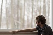 Depressiv blickender Mann am Fenster